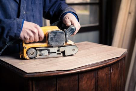 Man refinishing table with a belt sander
