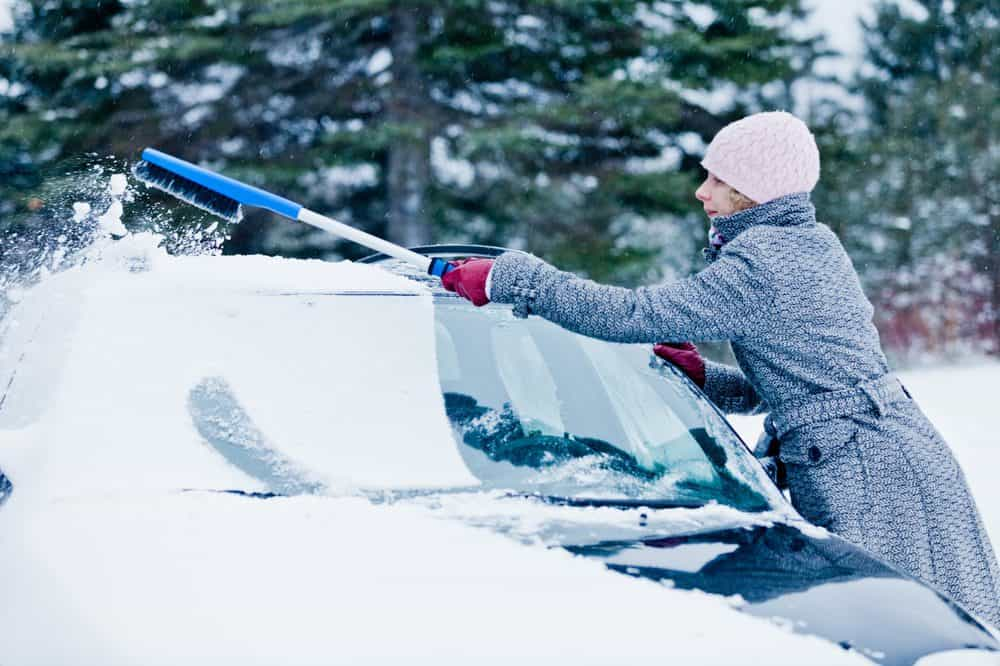 Woman removing snow from a car with a snow brush