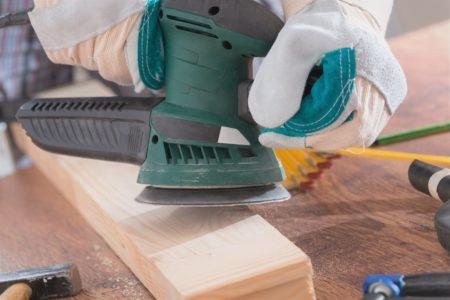 Sanding plank of wood with orbital sander