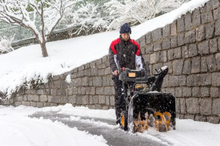 Man removing snow with a two-stage snow blower