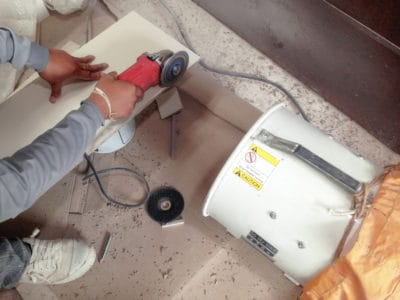Woodworker cutting wood with a grinder and a dust collector on the side
