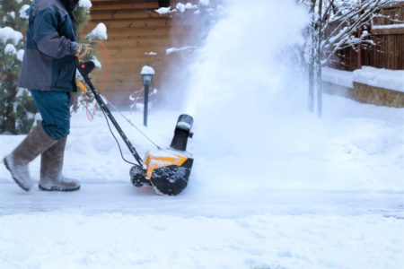 Man clearing snow with electric snow blower