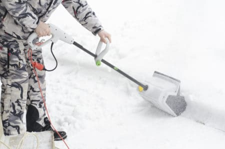 Man removing snow with electric snow shovel