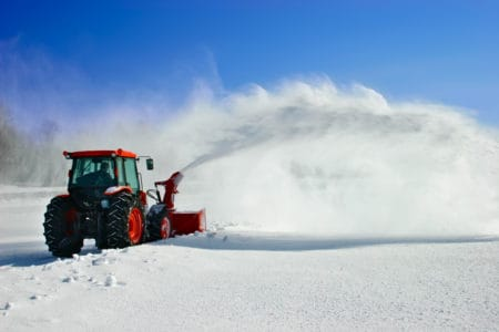 Tractor snow blower removing deep snow