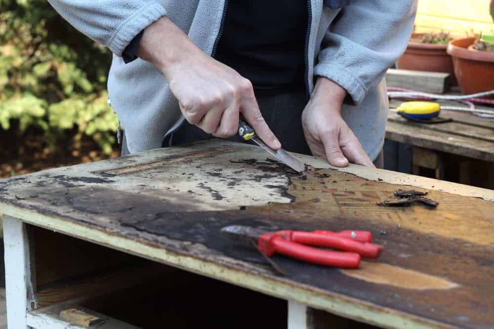 Woman restoring an old, damaged dresser