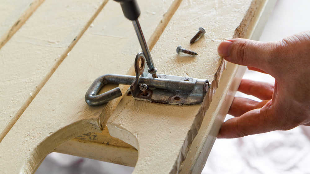 Man holding a wooden gate while unscrewing the rusty screws from a lock bolt.