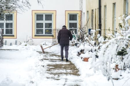 Man sweeping snow from the driveway