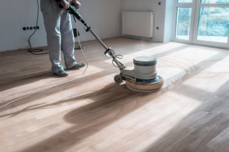 Man sanding hardwood floor with an orbital sander