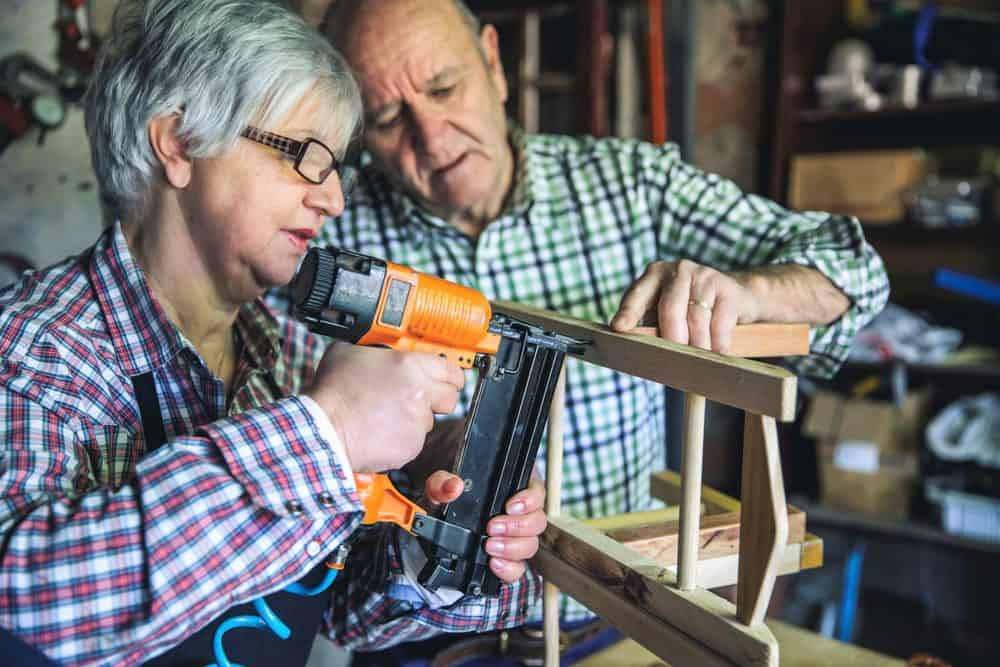 Husband teaching his wife how to use a staple gun