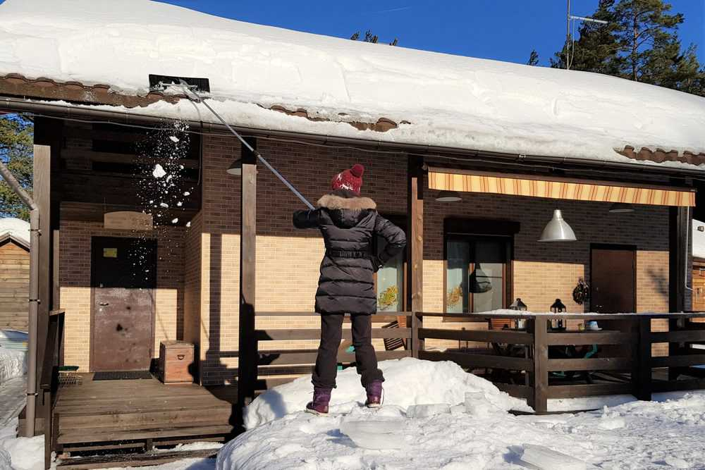 Woman cleans snow with shovel from roof of house