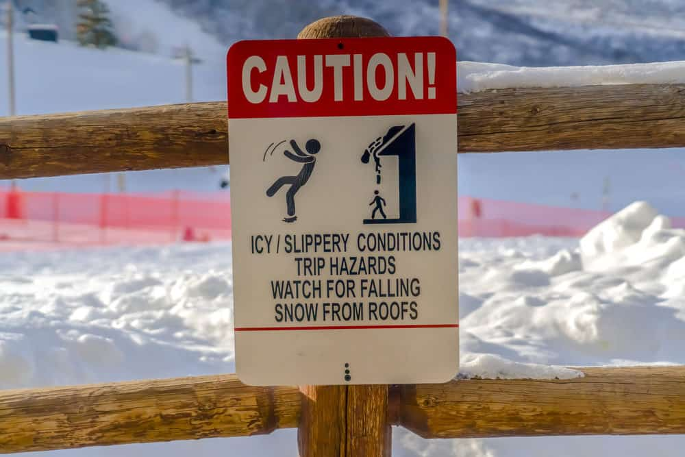 Caution sign on wooden fence against snow