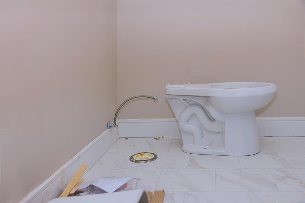 Plumber installing toilet bowl seat in restroom