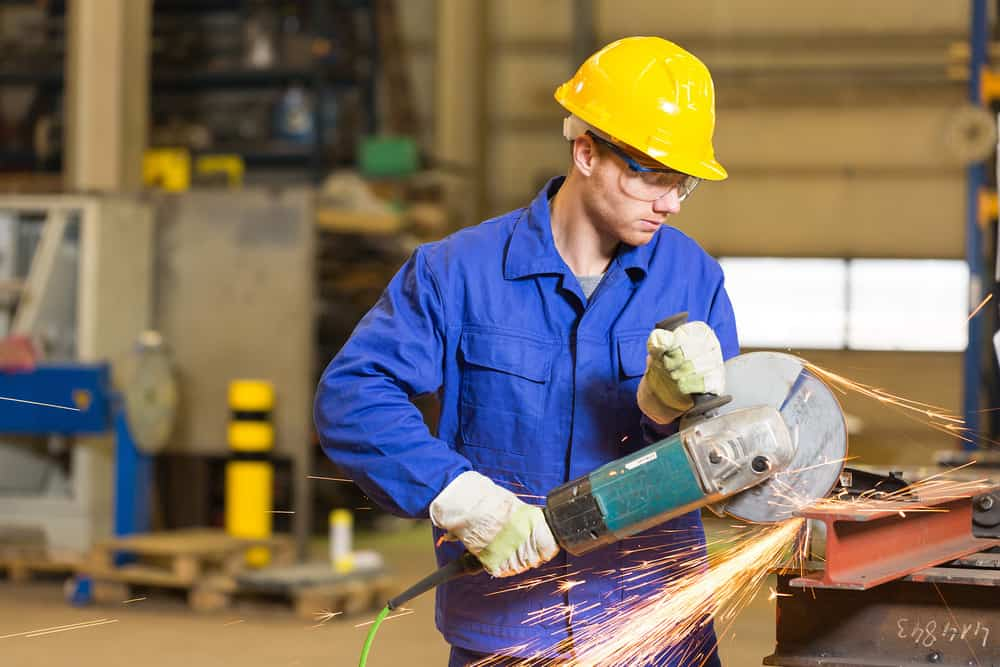 Steel construction worker cutting metal with angle grinder