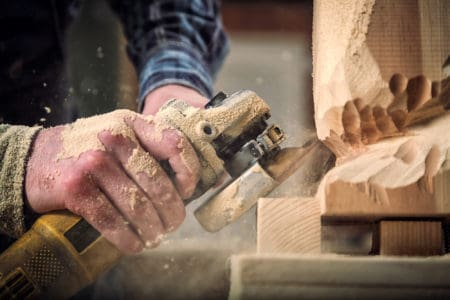 Carpenter in work clothes using angle grinder to cut wood