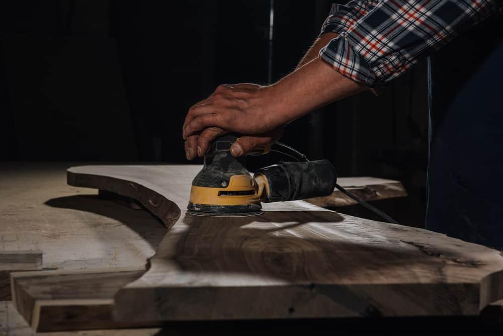 Person sanding wood with orbital sander
