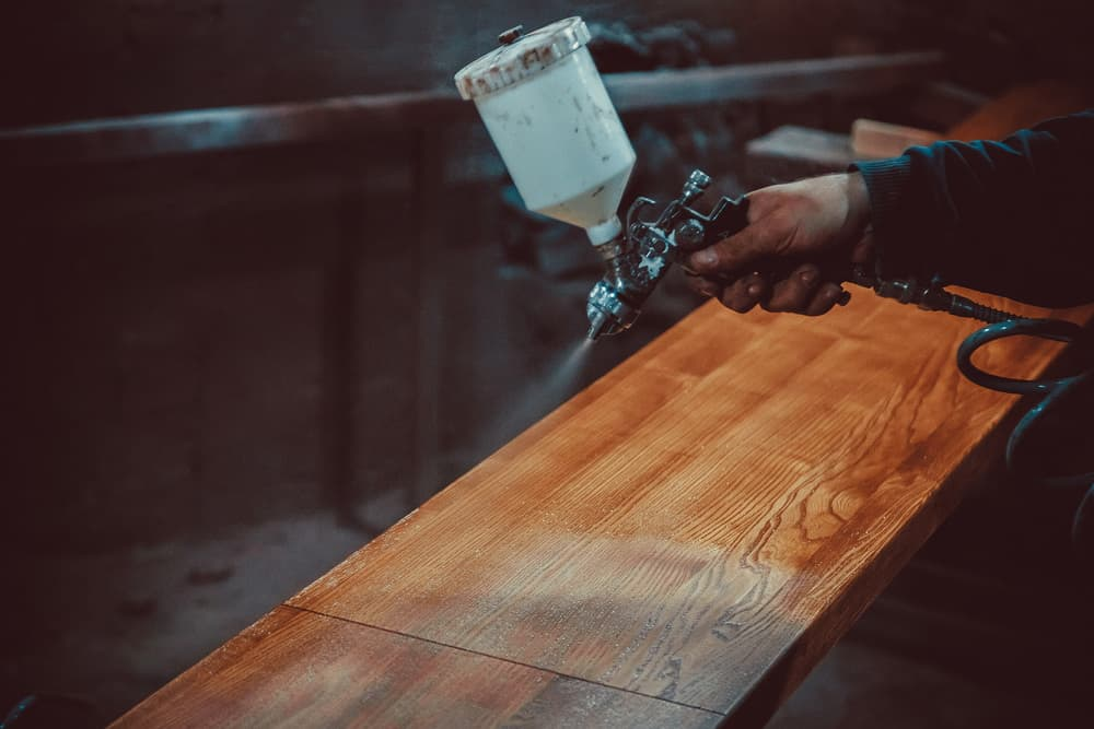Master painter in a factory - industrial painting wood with spray gun
