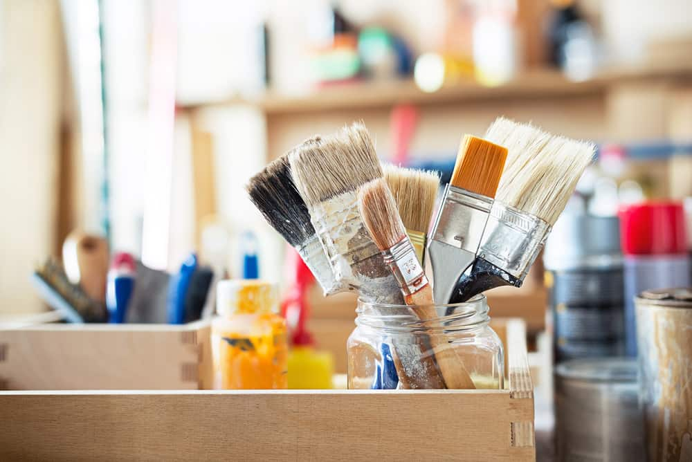 Paint brushes in a jar on the workshop table
