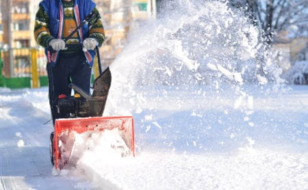Man clearing snow using snow blower