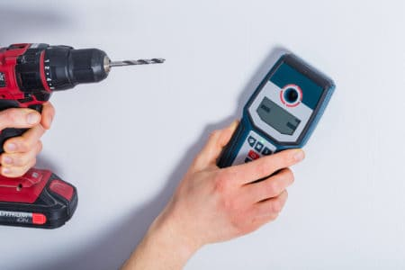 Man scanning a wall with a stud finder while holding a drill in the other hand
