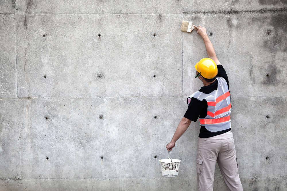 Painter working on an old concrete wall