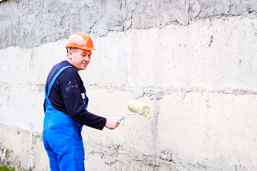 A builder with a roller painting concrete wall