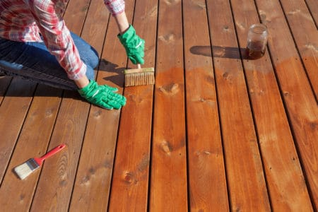 Person applying varnish on a wooden deck