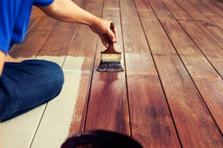 Person painting a deck with a paint brush