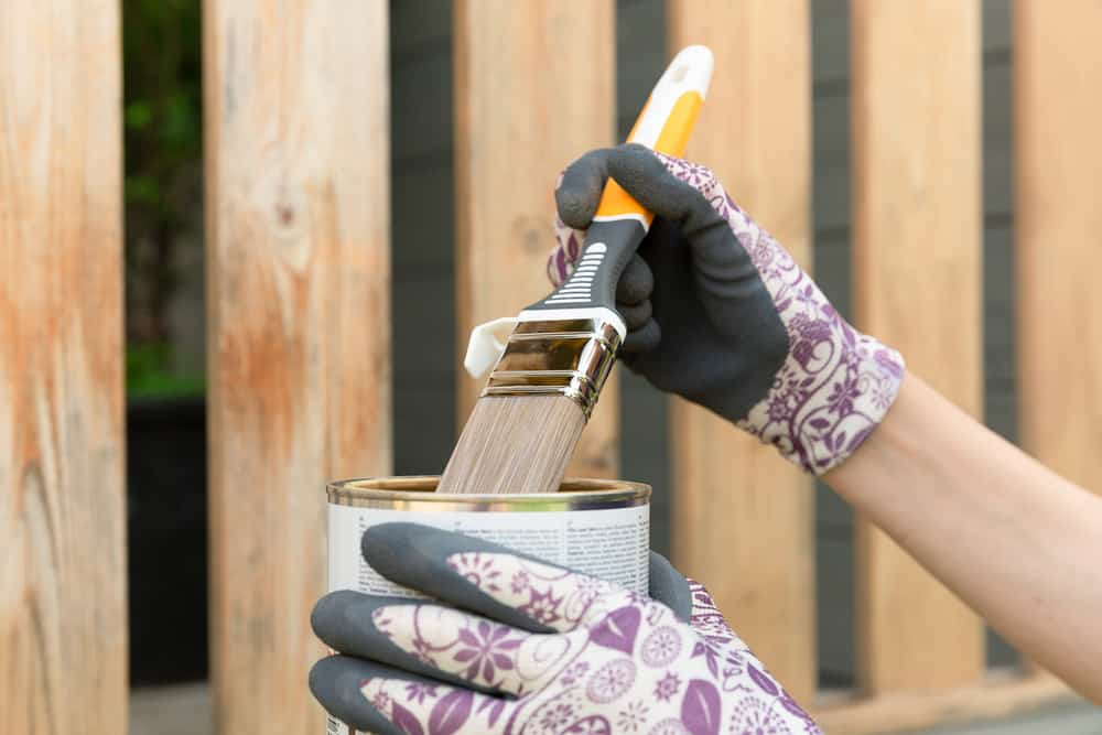 Woman's hand with a paintbrush painting a wooden fence