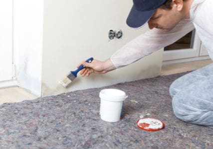 Painter covering damp walls