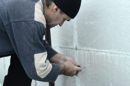 A worker creates holes in the wall for subsequent drilling