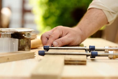 Carpenter hands at work with clamp