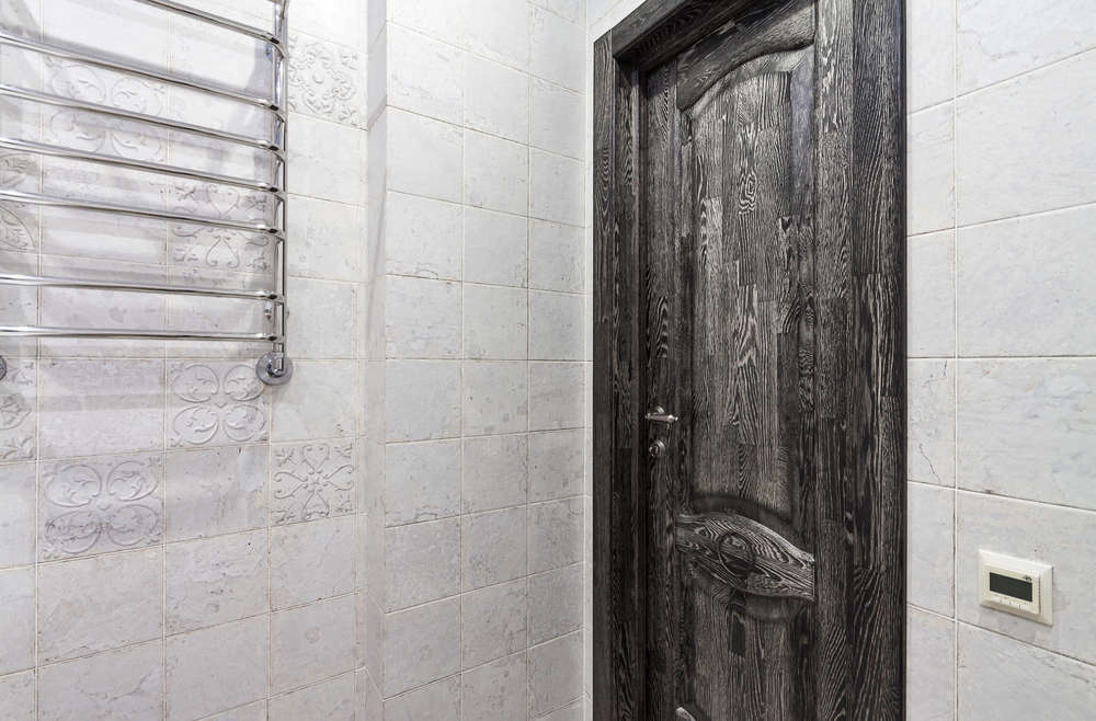 Classical closed wooden black oak door in white tiled mosaic wall of the bathroom