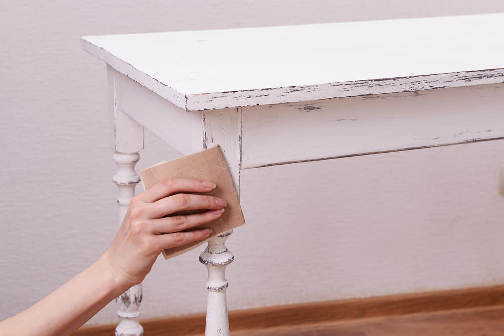 Female hand removing paint from wooden tabel
