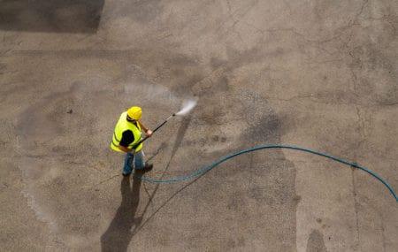 Worker pressure washing concrete floor