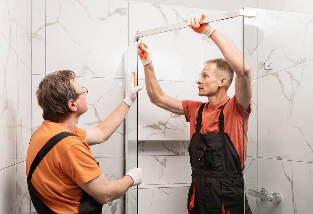 Workers connecting shower doors