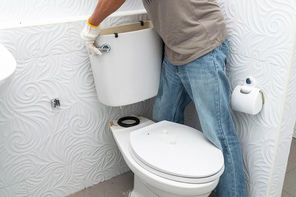 Man holding an empty toilet tank