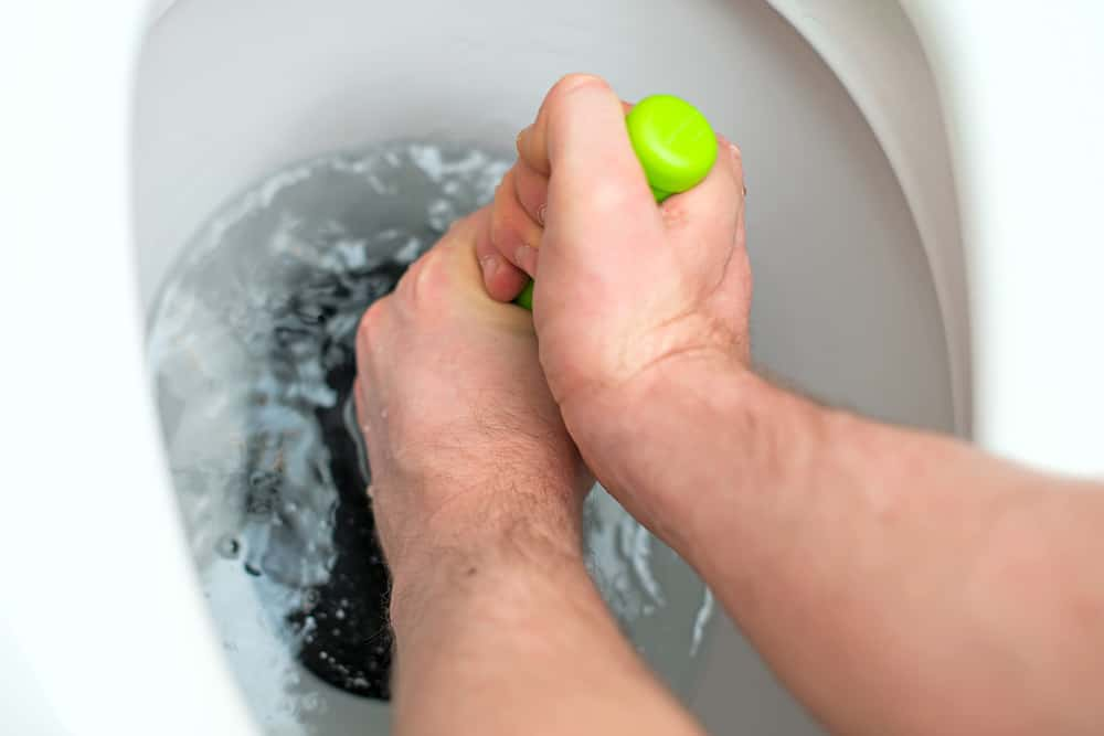 Person uncloging a toilet with a plunger