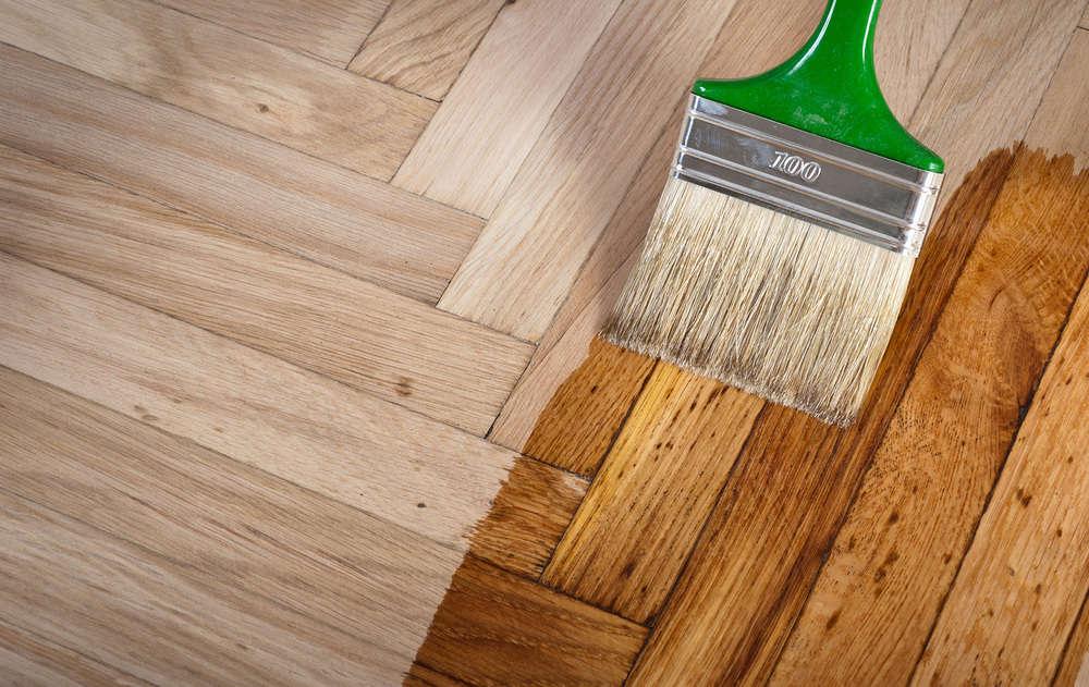 Varnishing hardwood floor with a paint brush